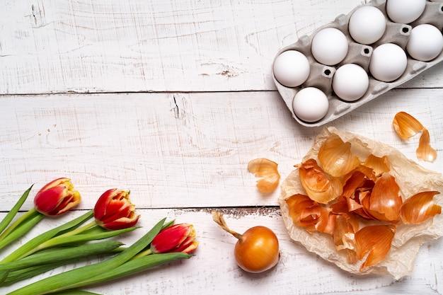 Пасхальные яйца расписаны натуральным яичным красителем из фруктов и овощей, яйца расписаны луковой шелухой на белом деревянном столе и красными тюльпанами, копия пространства