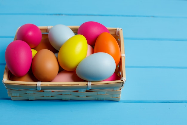 Easter eggs in the basket on blue wooden wall