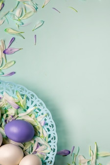 Easter eggs in a basket and colorful petals of spring flowers on a light green background.