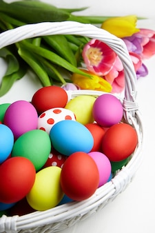 Easter eggs in basket and spring colorful flowers on white wooden table
