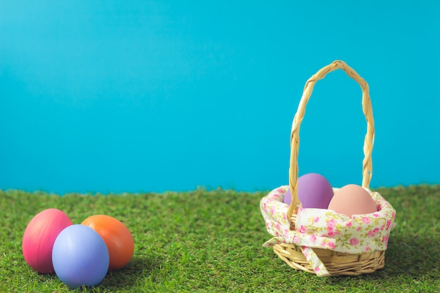 Easter eggs in a basket weave wood on the green grass.