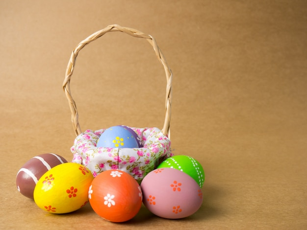 Easter eggs in a basket weave wood on the left corner on brown