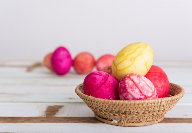 Easter eggs in basket on wooden table top background