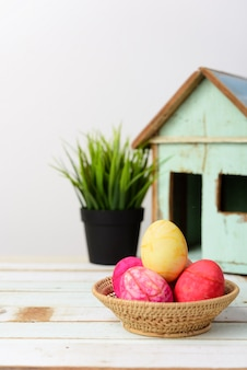 Easter eggs in basket on wooden table top with vintage house background