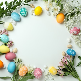 Easter eggs and beautiful flowers on white background, space for text