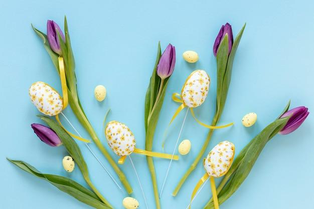 Easter eggs beside tulips on table