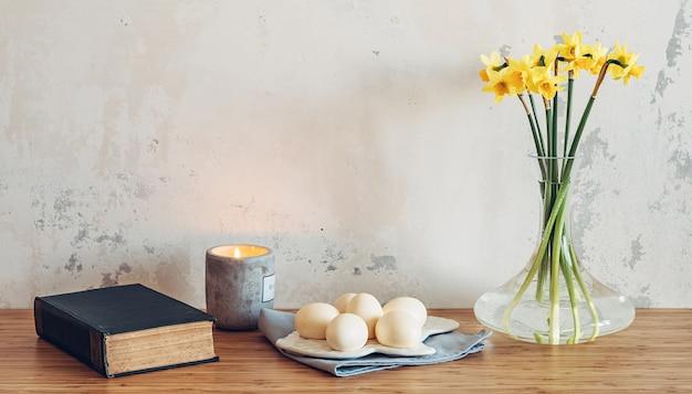 壁の背景にテーブルの上のイースターエッグ、聖書、春の花。