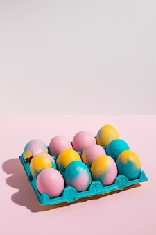 Easter eggs in big rack on pink table
