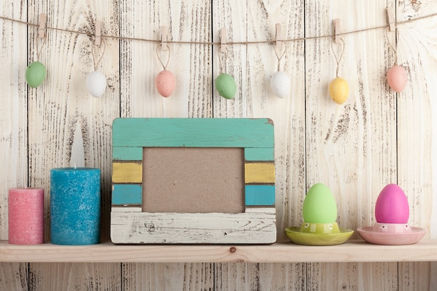Easter eggs, blank frame and candles on wooden background
