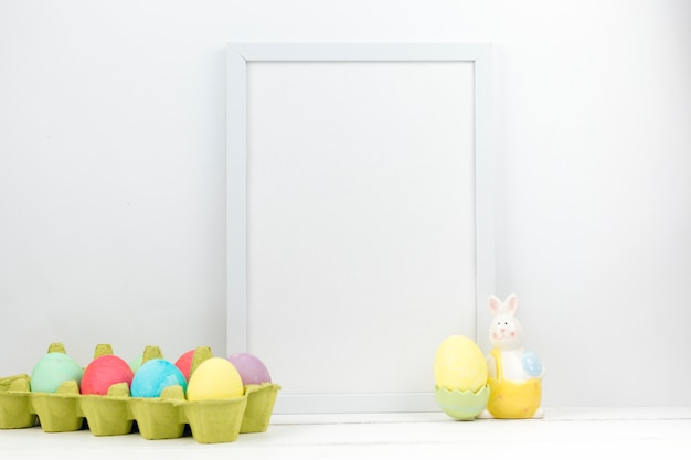 Easter eggs in box with blank frame on table
