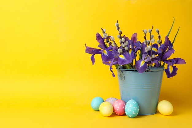 Easter eggs and bucket with flowers on yellow surface