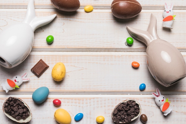 Easter eggs; bunnies figurine; candies and choco chips on wooden textured backdrop with space in the center for writing the text