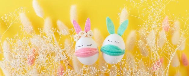 黄色の壁に医療用マスクでイースターエッグのウサギ。笑顔とお祝いの概念。