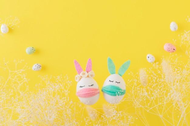 노란색 벽에 보호 마스크에 부활절 달걀 토끼. 코로나 바이러스 전염병 개념.
