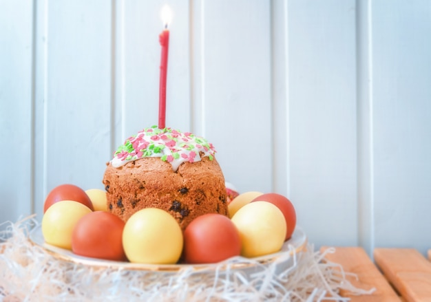 Easter eggs and cake with candle on the bright wooden background