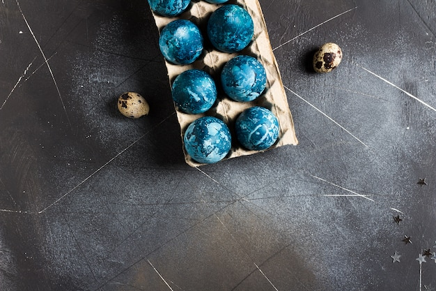 Easter eggs in cardboard packaging painted by hand in blue color