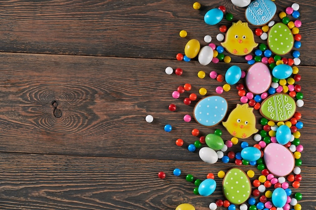 Easter eggs and chicken cookies over wooden background