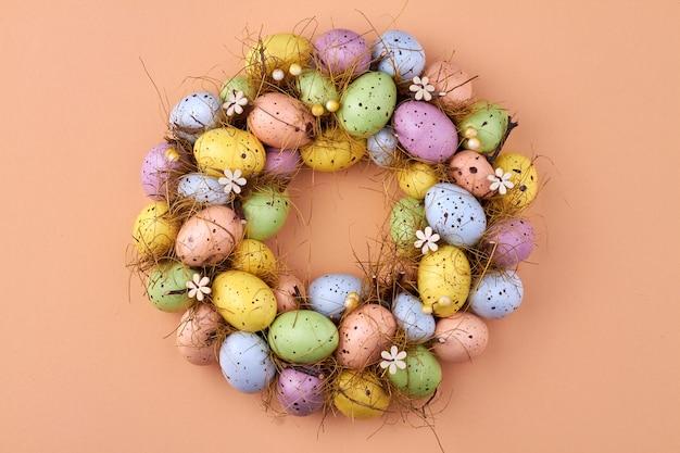Пасхальные яйца круг на бежевом фоне. вид сверху декоративные разноцветные яйца.
