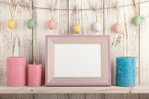 Easter eggs on clothespins, candles and blank wooden frame