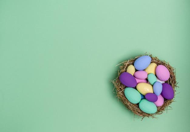 緑の背景、コピースペース、フラットレイアウトのわらで作られた装飾的な巣の色のイースターエッグ