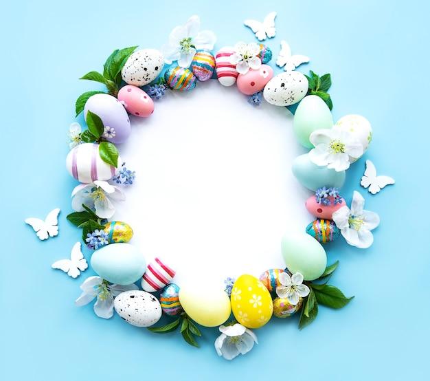 イースターエッグ、パステルブルーのテーブルに色とりどりの花。春、イースターのコンセプト。フラットレイ、上面図、コピースペース、円
