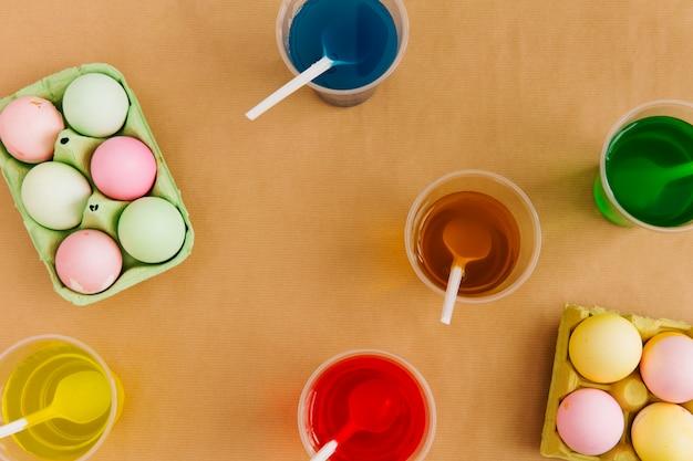 Uova di pasqua in contenitori vicino a tazze con liquido colorante colorato