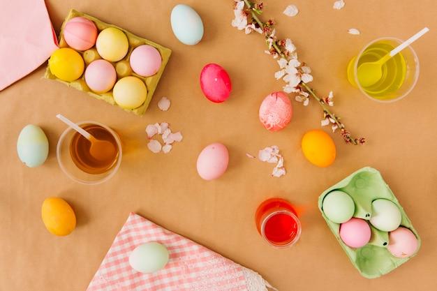Uova di pasqua in contenitori vicino a tazze con liquido di tintura, tovagliolo e fiore ramoscello