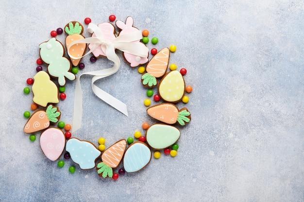 Пасхальные яйца, печенье и красочные сладости в форме кругового венка на сером столе. минимальная концепция праздника с копией пространства для текста. плоская планировка