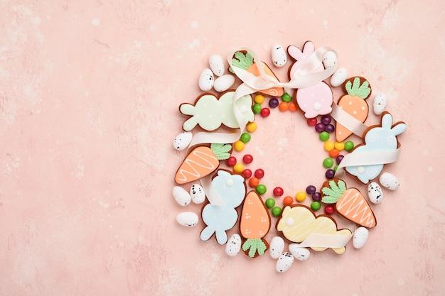 Пасхальные яйца, печенье и красочные сладости в форме кругового венка на розовом столе. минимальная концепция праздника с копией пространства для текста. плоская планировка