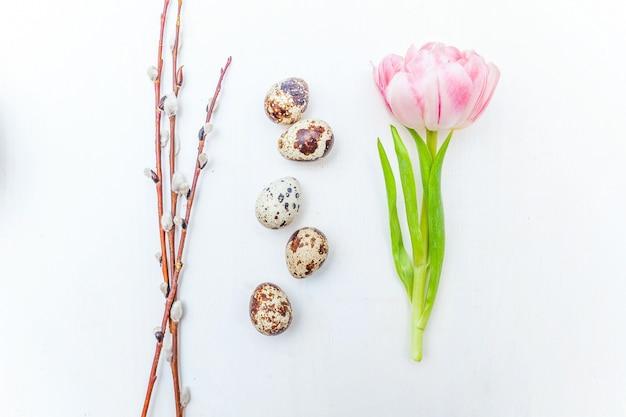 イースターエッグ綿柳の枝と素朴な白い木製の背景にピンクの新鮮なチューリップの花の花束