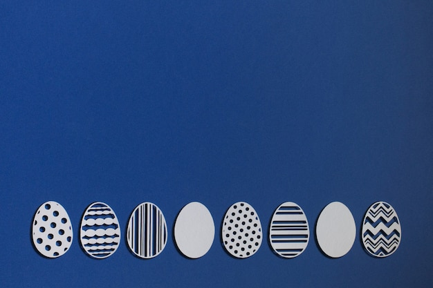 Easter eggs cut from paper on a classic blue background, color 2020 classic blue pantone