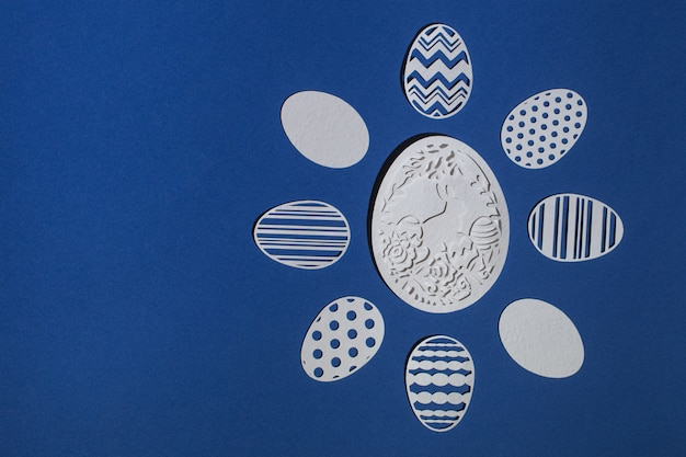 Вырезанные из бумаги пасхальные яйца на классическом синем фоне, цвет 2020 classic blue pantone