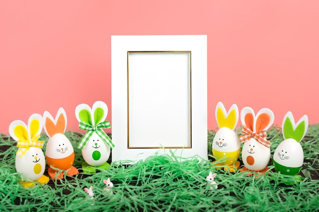 Easter eggs cute bunny, grass  and white photo frame on coral pink background.