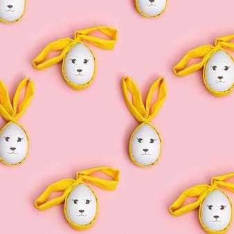 イースターエッグは布の耳をかわいいウサギとして飾りました。明るい色、春の休日のパターン