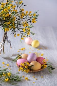 木製のテーブルに黄色い花で飾られたイースターエッグ