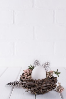 Easter eggs decoration. nest with white chicken egg. happy easter  or spring greeting card