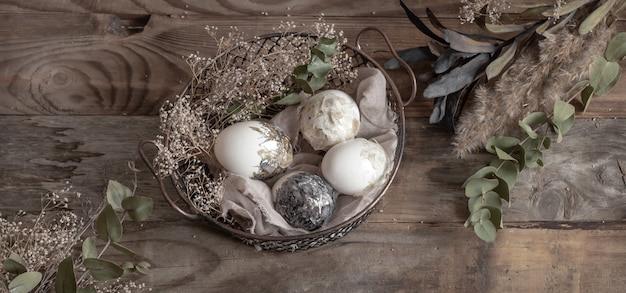 Easter eggs in a decorative basket with dried flowers on a wooden table. happy easter concept.