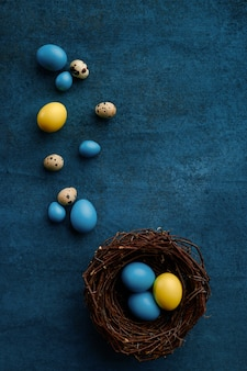 Easter eggs in decorative nest on blue cloth background