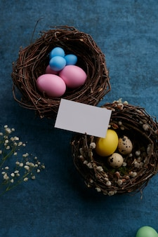Easter eggs in decorative nests and greeting card on blue cloth background