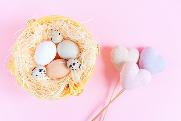 Easter eggs of different colors and quail eggs in a straw nest and decorative textile hearts on a pink surface, top view, flat lay. easter concept.
