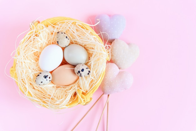 Easter eggs of different colors and quail eggs in a straw nest and decorative textile hearts on a pink surface