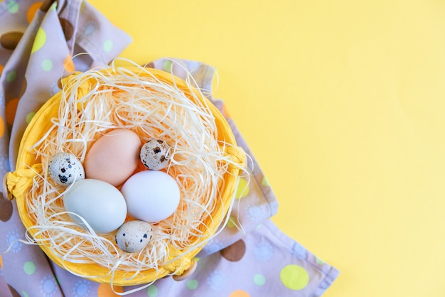 Easter eggs of different colors and quail eggs in a wicker basket on stylish napkin on a yellow background, top view. flat lay. easter concept.