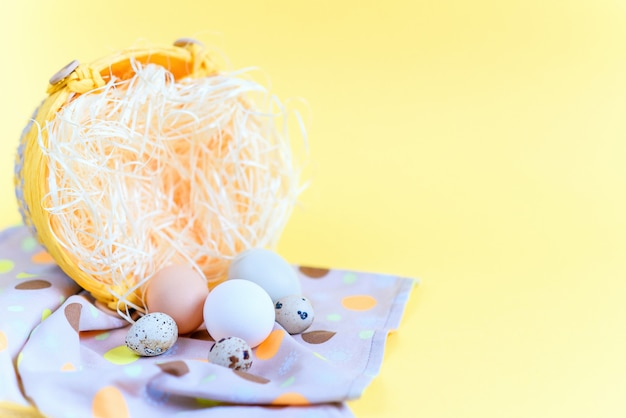 Easter eggs of different colors and quail eggs in a wicker basket on stylish napkin on a yellow background, top view with free copy space. easter concept.
