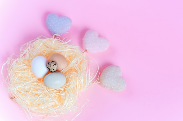 Easter eggs of different colors in a straw nest and decorative textile hearts on a pink background.