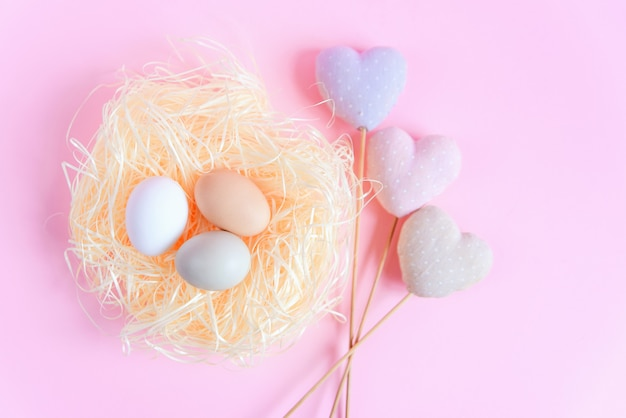 Easter eggs of different colors in a straw nest and decorative textile hearts on a pink surface, top view, flat lay. easter concept.