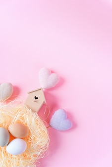 Easter eggs of different colors in a straw nest, wooden bird feeder and decorative textile hearts on a pink background,