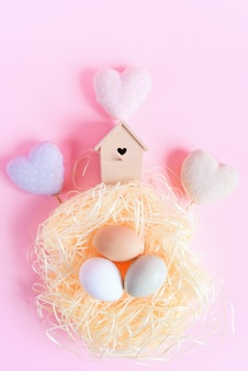 Easter eggs of different colors in a straw nest, wooden bird feeder and decorative textile hearts on a pink surface, top view, flat lay. easter concept.