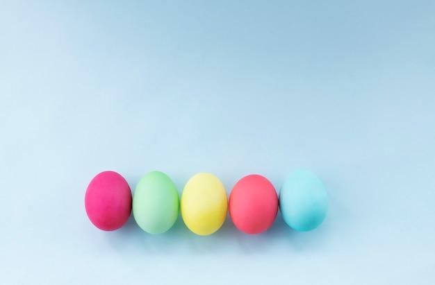 Пасхальные яйца, окрашенные в пастельные тона на голубом фоне изображение с копией пространства