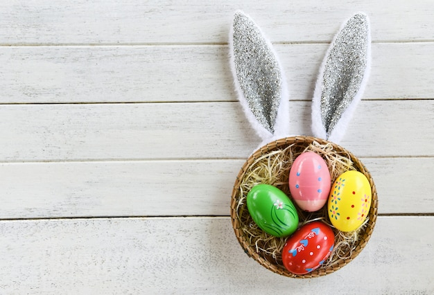 Easter eggs and easter bunny ear rabbit in basket nest