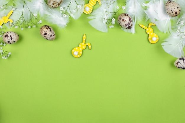 Пасхальные яйца, пасхальный кролик, перепелиные яйца, цветы и белые перья на зеленом фоне.